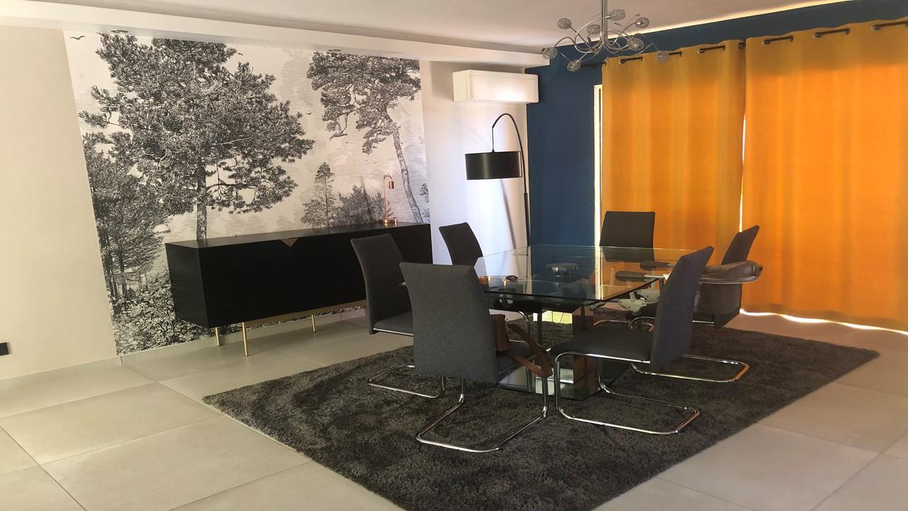 Décoration et agencement d'une villa à la Seyne sur mer- La salle à manger contemporaine avec mur bleu canard et rideaux moutarde, par Myll décors , Agence de décoration à Aix en Provence et dans le Var